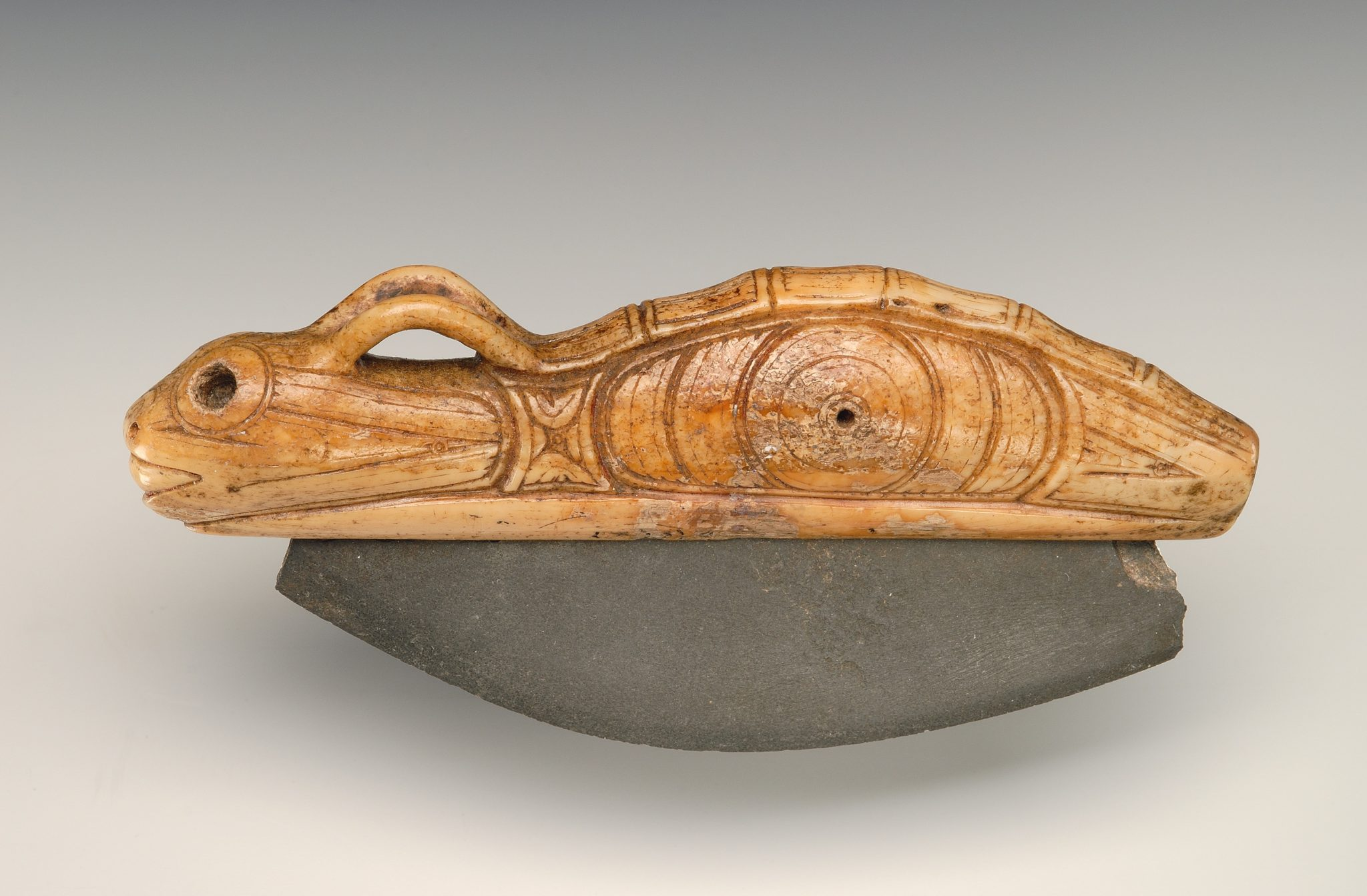 Ulu knife with zoomorphic handle from the ancient Eskimo burial site Ekven (OBS II-III). Material: stone, walrus tusk. State Museum of Oriental Art, Moscow (photo Ye. Zheltov).